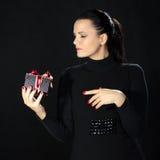 De mooie vrouw toont rente voor een giftdoos Stock Foto's