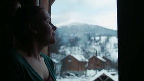 De mooie vrouw trekt hart bij een venster stock video