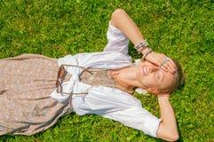 De mooie vrouw van de bohostijl met heel wat toebehoren ligt op groen gras Gelukkige mometn stock foto