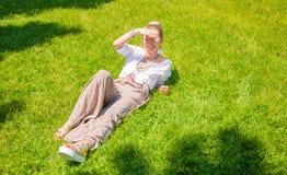 De mooie vrouw van de bohostijl met toebehoren geniet de zomer van zonnige dag op gras in park stock afbeelding