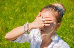 De mooie vrouw van de bohostijl met toebehoren geniet de zomer van zonnige dag in park Vrouwelijke handen met armbanden en ringen royalty-vrije stock afbeelding