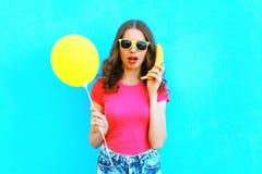De mooie vrouw van het manierportret met banaan en geel een luchtballon die pret over kleurrijke blauwe achtergrond hebben Royalty-vrije Stock Foto