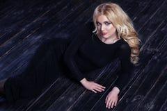 De mooie vrouw van het meisjesblonde in shikranom zwarte avondjurk op een donkere achtergrond Royalty-vrije Stock Foto