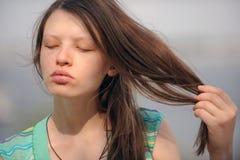 De mooie vrouw van Volgograd op de kust van de grote Russische rivier Volga blaast haar lippen op en toont mooi haar Stock Foto