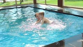 De mooie vrouw vangt weinig jongen die springend in pool Langzame Motie stock videobeelden