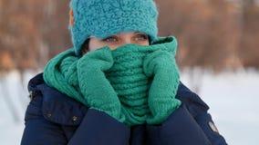 De mooie vrouw verbergt gebruikend haar sjaal in de winterpark stock footage