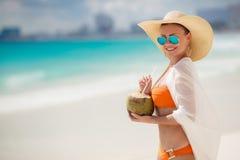 De mooie vrouw verwijdert dorst met kokosmelk Stock Foto's