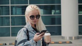 De mooie vrouw verzendt een tekstbericht gebruikend app op haar smartphone terwijl het lopen in het straat modelblonde stock footage