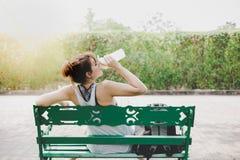 De mooie vrouw voelt geprobeerd en dorstig, it's zonnige dag Charmerend mooi meisje zit op bank bij park en neem een rust, voel royalty-vrije stock fotografie