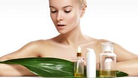 De mooie vrouw vraagt organische schoonheidsmiddel en oliën schoonheid aan Kuuroord en wellness Schone huid, glanzend haar Gezond royalty-vrije stock afbeelding