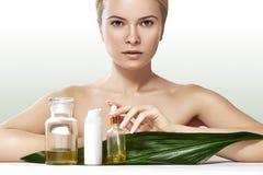 De mooie vrouw vraagt organische schoonheidsmiddel en oliën schoonheid aan Kuuroord en wellness Schone huid, glanzend haar Gezond royalty-vrije stock foto's