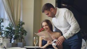 De mooie vrouw wacht op haar vriend in restaurant, komt hij en geeft haar bloemen, kussend haar Gelukkig meisje stock video