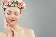 De mooie vrouw wat betreft haar ziet haar hand onder ogen Vrij spontaan meisje met bloemen Gezichtsbehandeling, gezicht die, het  stock afbeeldingen