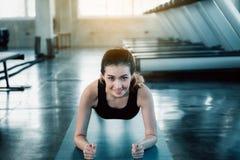 De mooie vrouw werkt in geschiktheidsgymnastiek uit , Planking de Aantrekkelijke jonge vrouw opdrukoefeningoefening voor tredmole royalty-vrije stock fotografie