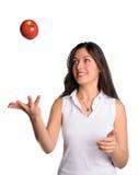 De mooie vrouw werpt appel in geïsoleerde lucht Stock Afbeeldingen