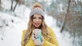 De mooie vrouw in de winterhoed geniet van de sneeuw en drinkt hete drank die zich buiten op de sneeuw in het bosmeisje bevinden stock videobeelden