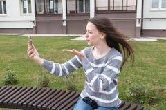 De mooie vrouw zegt vaarwel door video, golvend en verzendt een kus, uitnodigend mobiele telefoon stock fotografie