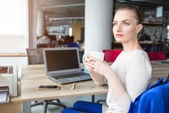 De mooie vrouw zit als voorzitter en houdt een kop thee Zij nam een pauze na wat bedrijvige tijd Zij is stock fotografie