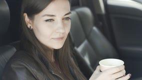 De mooie vrouw zit in auto, drinkt uit koffie, kijkt venster en glimlacht stock video