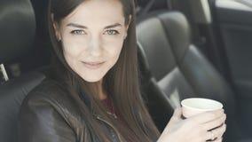De mooie vrouw zit in auto, halen de dranken koffie weg, bekijkt camera en glimlacht stock videobeelden