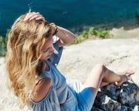 De mooie vrouw zit op de rand van de klip boven overzeese coas Royalty-vrije Stock Foto