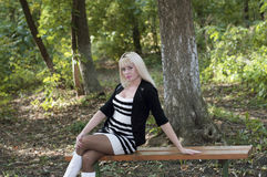 De mooie vrouw zit op een bank in de herfstpark Royalty-vrije Stock Afbeelding