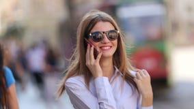 De mooie vrouw zoekt haar celtelefoon in haar modieuze zak Zij draagt klassieke kleren en haar lip is rood stock footage