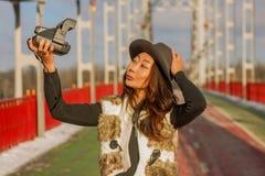 De mooie vrouw in zwarte hoed maakt een polaroid selfie op een brug in de winter in Europa stock afbeeldingen