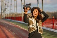 De mooie vrouw in zwarte hoed maakt een polaroid selfie op een brug in de winter in Europa stock foto's
