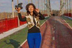 De mooie vrouw in zwarte hoed maakt een polaroid selfie op een brug in de winter in Europa royalty-vrije stock afbeeldingen