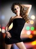De mooie vrouw in zwarte kleding stelt over nachtlichten Stock Foto's