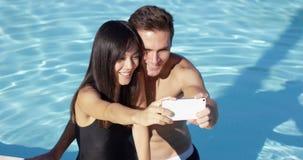 De mooie vrouw in zwarte zwemt kostuum neemt foto stock videobeelden