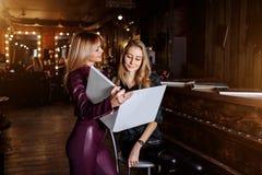 De mooie vrouwelijke beheerder van schoonheid en haarsalon met een glimlach toont het menu van de klantendienst royalty-vrije stock foto