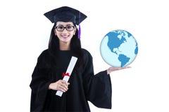 De mooie vrouwelijke gediplomeerde geïsoleerde bol van de holdingswereld - stock afbeeldingen