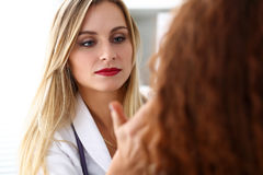 De mooie vrouwelijke geneeskunde arts met ernstig gezicht onderzoekt patie stock foto's