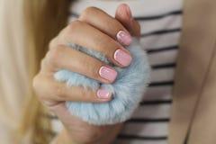 De mooie vrouwelijke hand met manicure houdt een blauwe pluizige bal Gevoelig roze nagellak met witte crescentsand en goed voorwa royalty-vrije stock foto