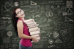 De mooie vrouwelijke student brengt stapel boeken in klasse Royalty-vrije Stock Foto
