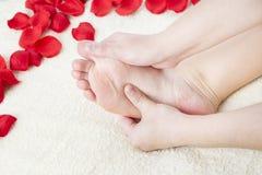 De mooie vrouwelijke voeten en namen bloemblaadjes toe Royalty-vrije Stock Afbeeldingen