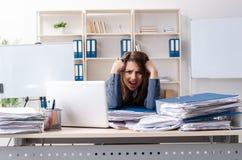 De mooie vrouwelijke werknemer ongelukkig met het bovenmatige werk stock fotografie