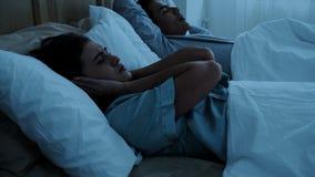De mooie vrouwen dichte oren wegens echtgenoot het snurken stock foto