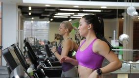 De mooie vrouwen oefenen op tredmolen in moderne sportclub uit stock videobeelden