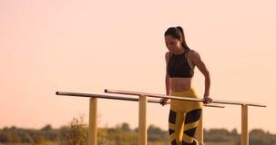 De mooie vrouwenatleet bij zonsondergang voert opdrukoefeningen op een parallelle rekstok uit stock video