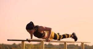 De mooie vrouwenatleet bij zonsondergang voert opdrukoefeningen op een parallelle rekstok uit stock footage
