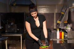 De mooie vrouwenchef-kok bereidt een hamburger in de keuken van het restaurant voor stock fotografie
