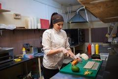 De mooie vrouwenchef-kok bereidt verse sushi in de keuken van het restaurant voor stock afbeelding