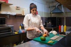 De mooie vrouwenchef-kok bereidt verse sushi in de keuken van het restaurant voor stock fotografie