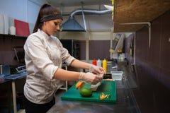 De mooie vrouwenchef-kok bereidt verse sushi in de keuken van het restaurant voor royalty-vrije stock afbeelding
