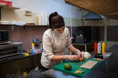 De mooie vrouwenchef-kok bereidt verse sushi in de keuken van het restaurant voor royalty-vrije stock fotografie