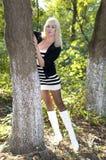 De mooie vrouwenkosten die een boom in het de herfsthout houden Stock Foto