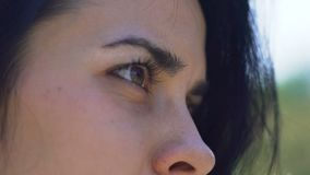 De mooie vrouwenogen openlucht, vrouw met het donkere knipoogje van haar bruine ogen ziet eruit, langzaam stock videobeelden